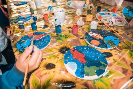 hand with a brush painting ceramic figure of rocket going to space.  developing art childrens games