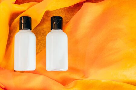 body lotion and shower gel in travel bottle on orange background Stok Fotoğraf - 129644722
