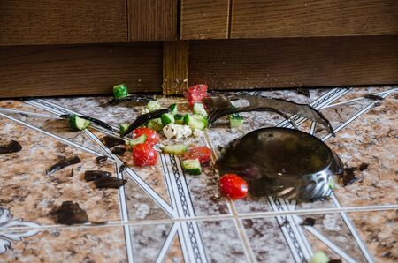 close up view of broken glass plate with food on floor. an accident in the kitchen. making salat problems 版權商用圖片