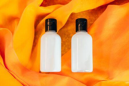two travel bottles of body lotion on orange background Stok Fotoğraf - 129644585