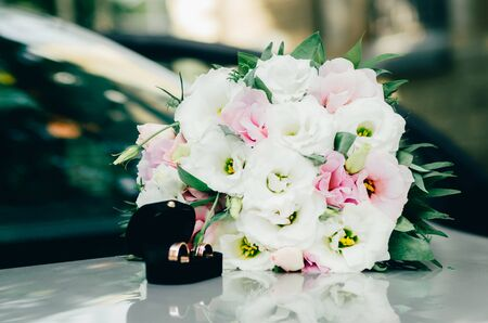 wedding rings in opened black box and white bride bouquet on the car. wedding moments background Stock Photo