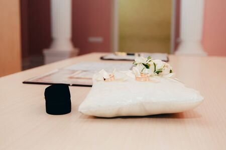 wedding rings on little decorated pillow in registry office. wedding moments background