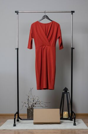 New red dress on hanger on garment rack in fashion design studio with empty copyspace for writing your brand Reklamní fotografie