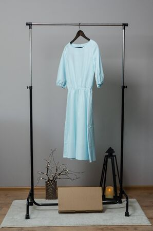 light blue long dress on hanger on garment rack in fashion design studio with mockup box for writing your brand