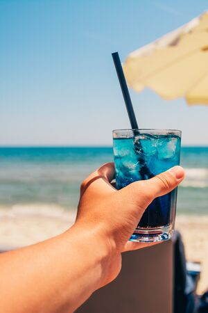 blue refreshing cocktail at the beach in the mans hand