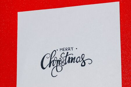 red background of merry christmas written on paper Stock Photo