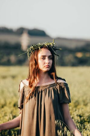 close up photo of woman in green dress standing in wheat field 写真素材 - 132455267