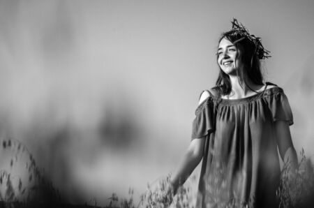 black and white photo of woman in dress and with wreath on her head is standing in wheat field