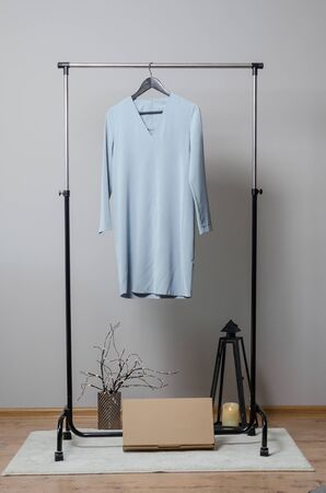 light blue dress on hanger on garment rack in fashion design studio with empty copyspace for writing your brand on the box