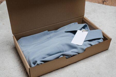 lichtblauwe jurk in een kartonnen doos met neplabel om je logo op te schrijven. thuisbezorging van bestelde kleding. het pakket uitpakken