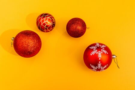 red christmas tree balls isolated on yellow background. choose the color for decorating your christmas tree with toys