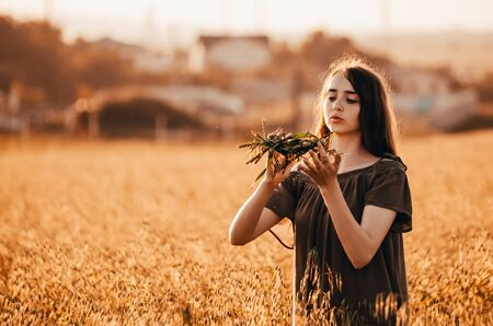 young woman ia making a wreath and is standing in golden wheat field