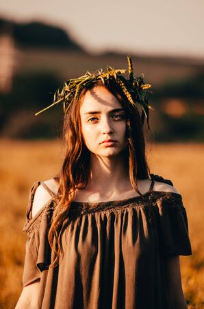 young woman in dress and with wreath on her head is standing in wheat field and looking in the camera 写真素材 - 132455251