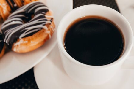 cup of coffee and donuts with chocolate topping for breakfast. selective focus Foto de archivo