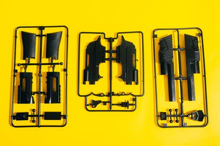 assemble toy handgun with bulllets from the parts concept on yellow background. Plastic model part kits from top view. Reklamní fotografie