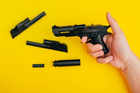 mans hands assembling toy handgun with bulllets from the parts from top view Reklamní fotografie