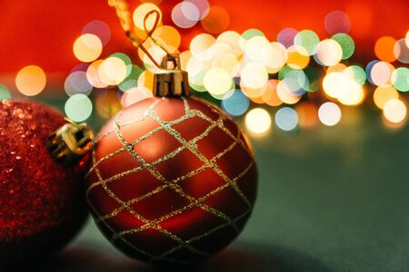 two red christmas tree balls with bokeh lights on background. fairy ans magical christmas mood