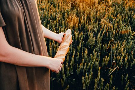 girl in dress with french baguette in green wheat field