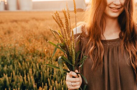 close up of womans smile in wheat field with shining sun 写真素材 - 132935389