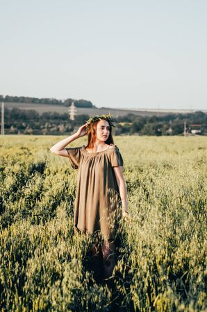 young woman in dress and with wreath on her head is standing in wheat field 写真素材 - 132936069