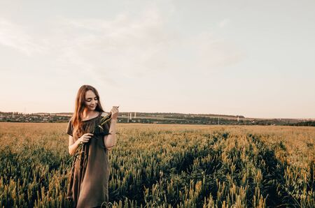young woman ia making a wreath and is standing in golden wheat field. feel the nature concept 写真素材 - 132935808