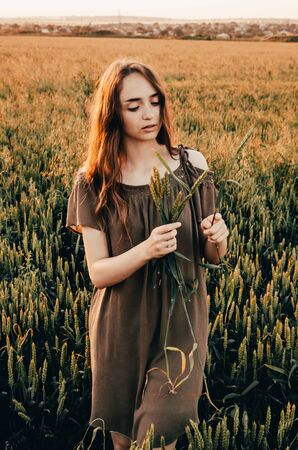 woman in green dress stands smilling in wheat field with shining sun