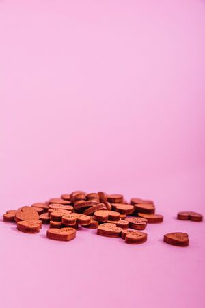 tiny wooden hearts with love written on them isolared on pink background. symbol of love concept