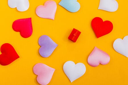 a miniature toy house with hearts around isolated on yellow background. A symbol of a home where love reigns. Imagens - 133634167