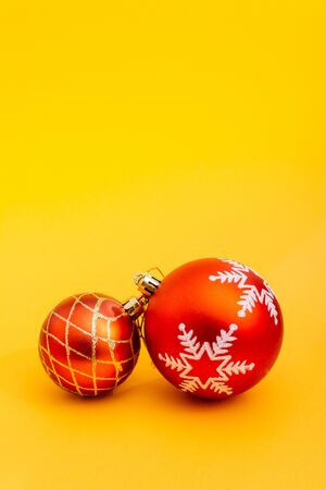 two red christmas tree balls isolated on yellow background from top view Imagens - 133634174