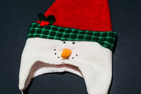 top view of christmas hat with snowman isolated on black background. christmas unique and thematic clothes Imagens - 133634173