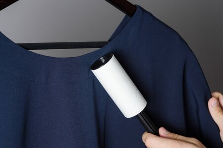 cleaning the dress with adhesive sticky roller. Domestic cleaning tool for getting rid of dandruff, hair, debris, pet wool and fluff. One-time paper roller with adhered dust Imagens - 133634176