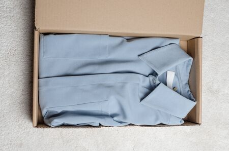 light blue dress in a cardboard box with mock label to write your logo . home delivery of odered clothes. unpacking the package from top view Imagens - 133634177