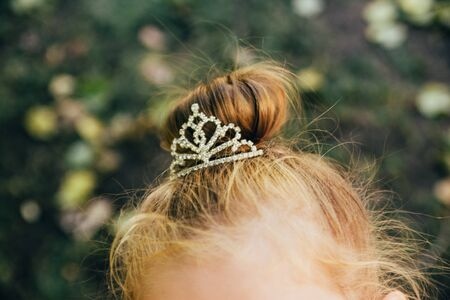 crown on girls head with blurred green leaves on background. being a princess concept Imagens - 133634216