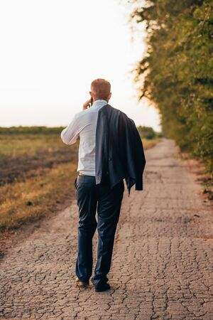 businessman walking in the quite place outside and talking on the phone. meditating concept Imagens - 133634217