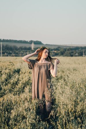 woman in green dress walks on path in wheat field in countryside Imagens - 133634223