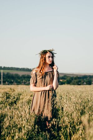 woman in green dress and with weath on her head walks on path in wheat field in countryside