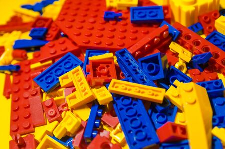 colored toy bricks for kids on the floor background. Playing in plastic lego concept. Pieces and elements of constructor toys. Imagens - 134215684