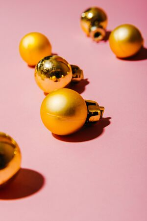 small golden christmas tree balls isolated on pink background Imagens - 134195421