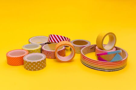 a mess of colorful washi tapes isolated on yellow background.