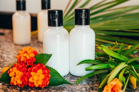 shower gel, shampoo and body lotion in small tubes. travel bottle set mock up with tropic flowers and palm leaves Imagens - 134195333