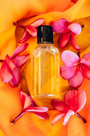 close up view of shampoo in small travel tube in hotel bathroom on orange towel with exotic flowers Imagens - 134195335