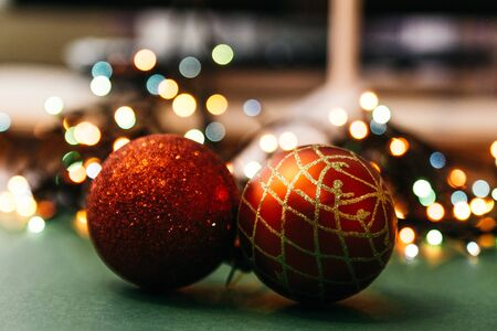 two red christmas tree balls with bokeh lights on background. fairy ans magical christmas mood. selective focus