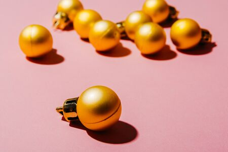 small golden christmas tree balls isolated on pink background Imagens