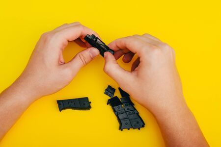 mans hands assembling toy handgun with bulllets from the parts from top view Foto de archivo