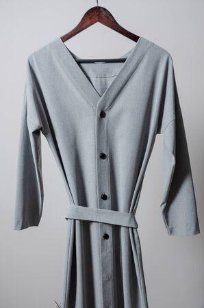 grey long button dress on hanger on garment rack in fashion design studio