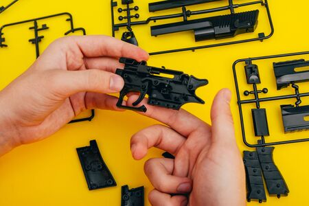 assemble toy handgun with bulllets from the parts concept on yellow background. Plastic model part kits  from top view. Imagens - 134195205