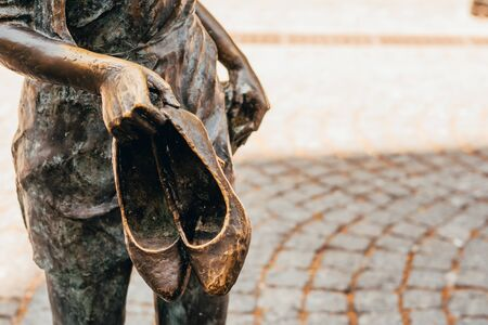 statue of female hands holding shoes outside Imagens - 134195029