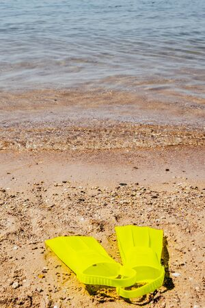 yellow swimming flippers on sand beach by the sea Imagens - 134194934