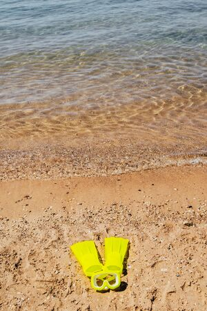 yellow swimming flippers and mask on sand beach by the sea Imagens - 134194936