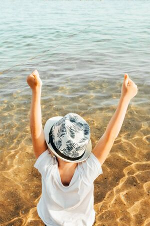 male panama hat on a boy who is sitting at the beach with hands up. kid is happy at summer time